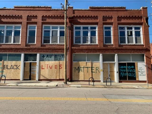 Photo of our Administrative Office in downtown Raleigh during the George Floyd protests. The windows are covered by boards with pro-Black Lives Matter slogans spray-painted on them.