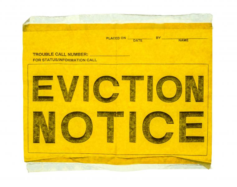 "A yellow piece of paper with ""eviction notice"" written in all capitals in a large font."